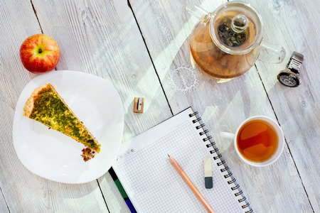 Diary, pencil, cup of tea, apple and watch on white wooden table Stock Photo