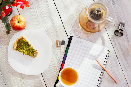 datebook: Datebook, pencil, cup of tea, chicken pie, apple, glass teapot and watch on white wooden table