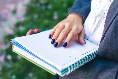 glossary: student girl with study sheets and glossary book close-up. Outdoor