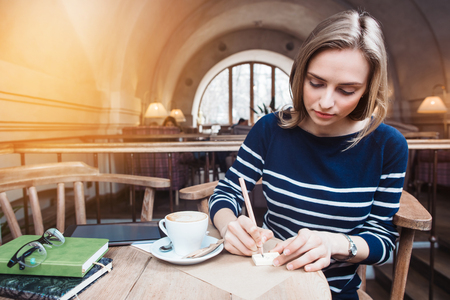 Young attractive woman writes reminders on stickies in cafe. Concept of planning personal traning schedule 写真素材 - 74673927