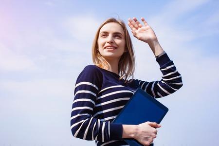 Glimlachende jonge aantrekkelijke blonde meid met de digitale tablet in handen wacht op het vriendje waving het een hand in de buurt van de rivier. Tablet met kopieerruimte op het scherm voor uw reclame-inhoud photo