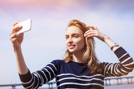 Attractive young woman, blonde, making selfie outdoors using smartphone and fast 4G internet connection while standing against river and bridge. Sunny spring day. photo