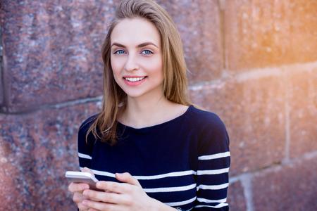 Mooie jonge vrouw, blondine, herinneringen buitenshuis met behulp van smartphone en snelle 4G internetverbinding, terwijl u tegen stenen muur staat. Zonnige lentedag. Granieten stenen muren photo