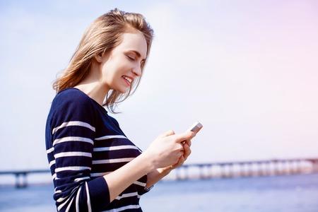 Mooie jonge vrouw, blondine, herinneringen buitenshuis met behulp van smartphone app en snelle 4G internetverbinding terwijl staan tegen rivier en brug. Zonnige lentedag photo