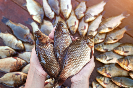 Three are fresh caught river fishes in hands. . Caught carp fish on wood. Catching freshwater fish on wood background. A lot of bream fish, crucian or roach on natural wood background. Background from big quantity river fishes on wooden boards laid out by a circle Stock Photo