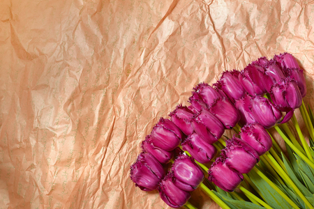 Fresh flower composition, bouquet purple tulips on craft paper background. Valentine, Womens, 8 march, birthday, mothers day present. Copy space, close up, top view.