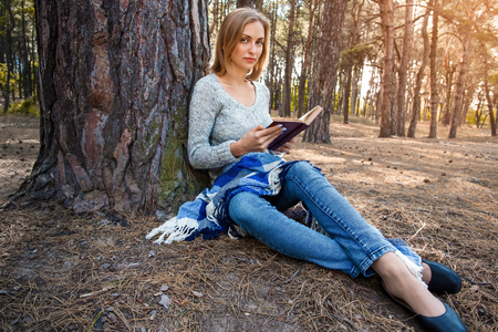 Beautiful blond girl resting in spring or autumn forest read book and sitting with a book. Confident caucasian young woman in casual clothes relaxing near big tree in park and holding book. Attractive female reads art or technical literature outdoors on nature in sunny day 版權商用圖片