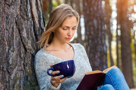 Beautiful blond girl resting in spring or autumn forest read book and sitting with cup of tea and book. Confident caucasian young woman in casual clothes relaxing near big tree in park and holding book. Attractive female reads art or technical literature outdoors on nature in sunny day