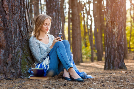 Beautiful blond girl resting in forest speak by cell phone and, sitting with cup of tea and book. Confident caucasian young woman in casual clothes relaxing near big tree in park and holding smartphone. Attractive female serfing internet outdoors on nature in sunny day
