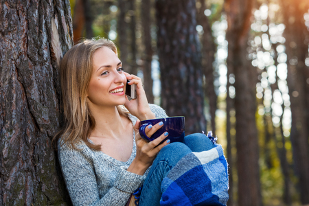 Beautiful blond girl resting in forest speak by cell phone and, sitting with cup of tea and book. Confident caucasian young woman in casual clothes relaxing near big tree in park and holding smartphone. Attractive female communicate outdoors on nature in sunny day