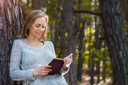Beautiful blond girl resting in spring or autumn forest read book and standing. Confident caucasian young woman in casual clothes relaxing near big tree in park and holding book. Attractive female reads art or technical literature outdoors on nature in sunny day