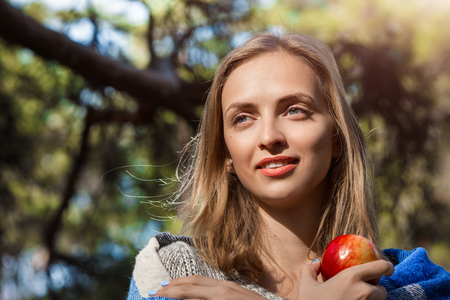 Beautiful blond girl resting in spring or autumn forest with red apple in her hands. Confident caucasian young woman in casual clothes relaxing in outdoor and holding apple. Attractive female outdoors on nature in sunny day 版權商用圖片