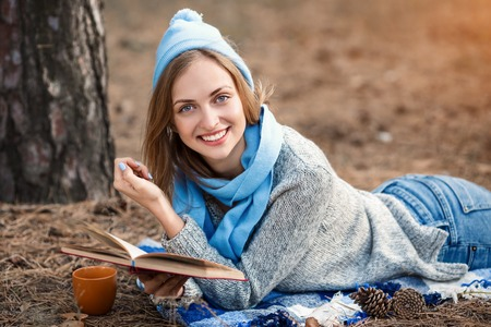 Beautiful blond girl resting in spring or autumn forest read book and, lie with cup of tea and book. Confident caucasian young woman in casual clothes in a blue cap and scarf relaxing near tree in park and holding book. Attractive female reads art or technikal literature outdoors on nature in sunny day 版權商用圖片