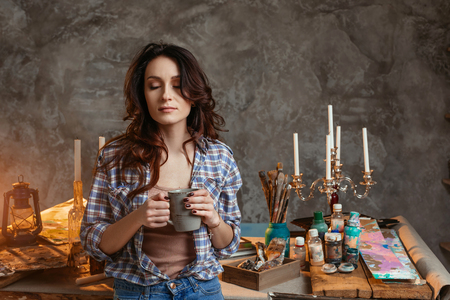 The young beautiful girl the artist blindly with a cup of coffee in the workshop. Reflects on images for the future pictures. Creative concept. Artist studio interior. Drawing supplies, oil paints, artist brushes, canvas, candle, oil lamp. Workshop or art class. Creative concept.