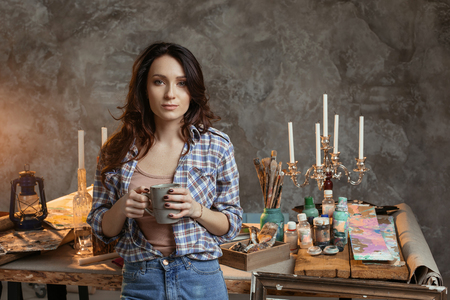 The young beautiful girl painter with a cup of coffee in the workshop. Before work reflects on images for the future pictures. Drawing supplies, oil paints, artist brushes, canvas, candle, oil lamp. Creative concept