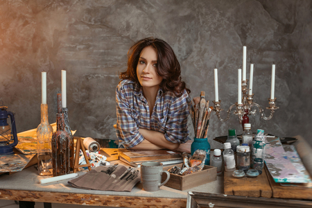 The beautiful young artist behind the desktop looks forward. The table is filled with art materials and accessories, books on art, an oil lamp and candelabrums with candles