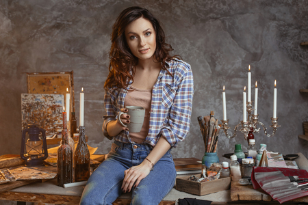The young beautiful artist sits on a table in the workshop with a cup of coffee. Looks in the camera. on table drawing supplies, oil and acrylic paints, artist brushes, Creative concept