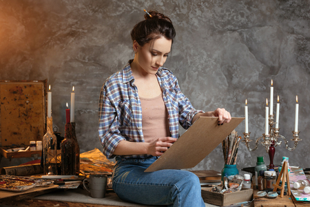 Woman painter sitting on the table, drawing and smiling. Creative concept. Drawing supplies, oil paints, artist brushes, canvas, candle, oil lamp.