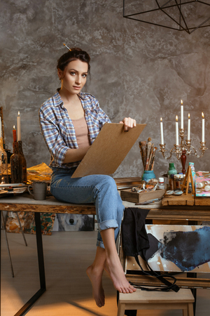 Girl painter sitting on the table, drawing and looking forward. Creative concept. Drawing supplies, oil paints, artist brushes, canvas, candle, oil lamp.