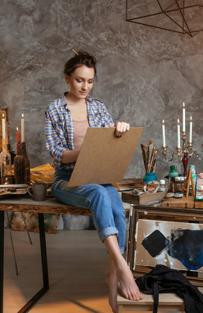 Female painter sitting on the table, drawing and smiling. Creative concept. Drawing supplies, oil paints, artist brushes, canvas, candle, oil lamp.