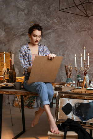 Attractive woman painter sitting on the table, drawing and smiling. Creative concept. Drawing supplies, artist brushes, canvas, candle, oil lamp.