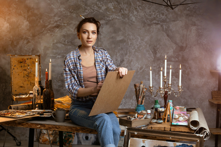 Woman painter sitting on the table, drawing and looking forward. Creative concept. Drawing supplies, oil paints, artist brushes, canvas, candle, oil lamp.