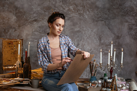 Woman painter sitting on the table, drawing. Creative concept. Drawing supplies, oil paints, artist brushes, canvas, candle. 版權商用圖片