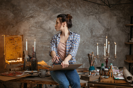Woman painter sitting on the table, drawing and looking left. Creative concept. Drawing supplies, oil paints, artist brushes, canvas, candle. 版權商用圖片