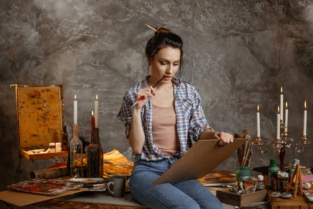 Woman painter sitting on the table, drawing and reflects over a sketch, holding a brush on a mouth. Creative concept. Drawing supplies, oil paints, artist brushes, canvas, candle.