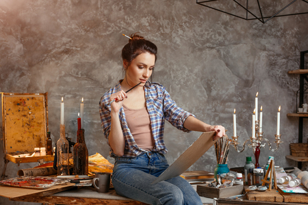 Good-looking cheerful professional young female artist working on new creative project, drawing, feeling inspired. Creative concept. Drawing supplies, oil paints, artist brushes, canvas, candle, oil lamp.