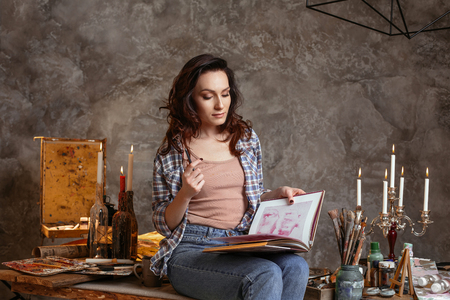 The beautiful young artist studies the book on art holds a pencil in hand. Horizontal portrait of the young painter. The workshop of the artist reminds workshops of ancient artists. Drawing supplies, oil paints, artist brushes, canvas, candle, oil lamp. Workshop or art class. Creative concept 版權商用圖片