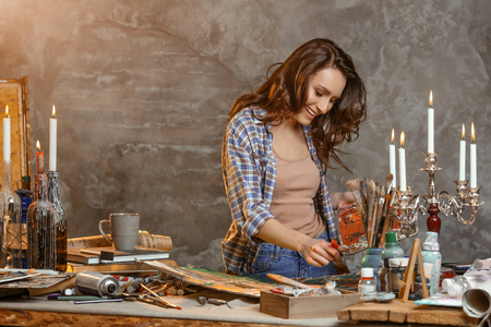 Indoor shot of beautiful brunette female painter wearing shirt, holding paint brush and palette in hands standing near easel, creating masterpiece, smiling joyfully while being glad to paint. Artist studio interior. Drawing supplies, oil paints, artist brushes, canvas, candle, oil lamp. Workshop or art class. Creative concept 版權商用圖片