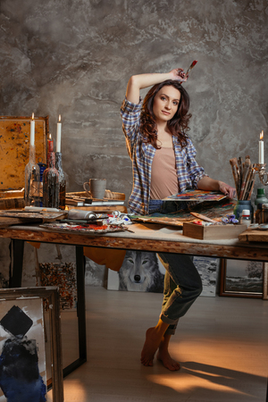 Young attractive artist makes a small break in the process of painting a new picture. In the hands of a woman a brush and a palette. Artist studio interior. Drawing supplies, oil paints, artist brushes, canvas, candle. Workshop or art class. Creative concept