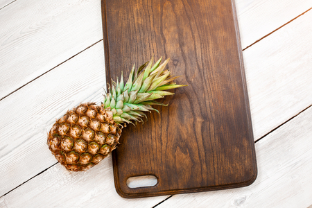Fresh ripe pineapple on a white wooden background, top view. From above 版權商用圖片