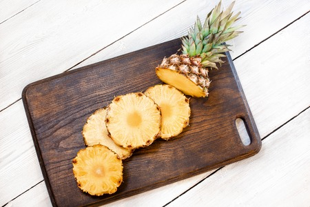 Sliced pineapple on brown and white wooden table.