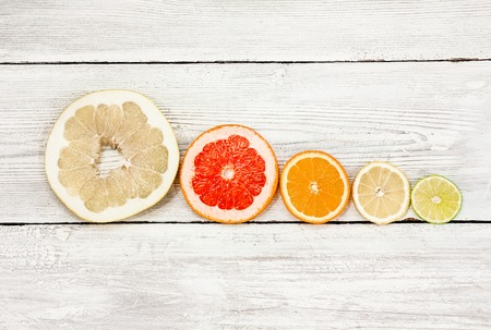 Citrus fruits slice on a wooden background, stacked pyramid. lemon, orange, lime, grapefruit, sweetie, pomelo, oroblanco