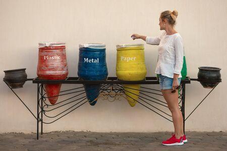 La giovane donna che smaltisce la spazzatura, gettandola in un contenitore decorativo giallo, è a destra. Bella donna in abbigliamento casual e scarpe da ginnastica si prende cura dell'ambiente. Lei fa un esempio su come aiutare la natura