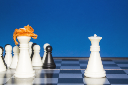 activism: Chess as a policy. White figure with red hair with a team against a lone white figure.