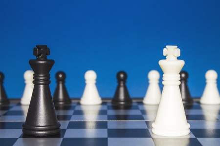 Chess as a policy. A lonely black figure against a lone white figure. A small group of the public looks from the outside. Stock Photo