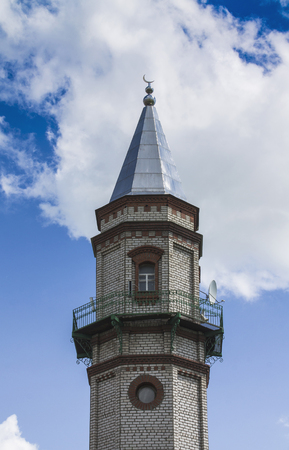 sunni: Mosque of Sunni Muslims. Minaret against the blue sky with white clouds.