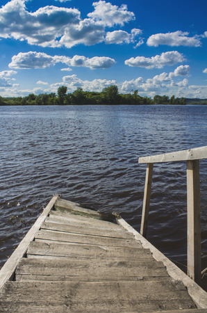 Wooden steps for boarding a boat go into the water under a blue sky with white clouds.