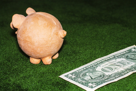 Tax day. Piggy bank with a dollar note against the green carpet background.