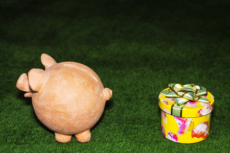 Tax day. Piggy bank with a yellow gift against the green carpet background.