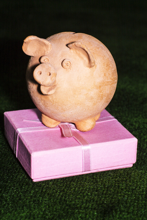 Tax day. Piggy bank with a pink gift box against the green carpet background. Stock Photo
