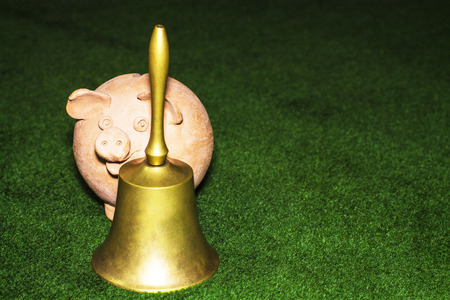 Tax day. Piggy bank with a bell against the green carpet background.