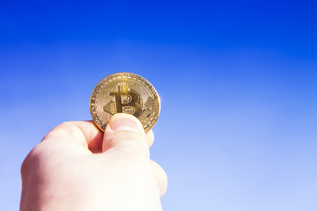 Crypto currency. Bitcoin. A hand raised up holds a gold coin bit coin against the blue sky. The suns rays are reflected in the coin.