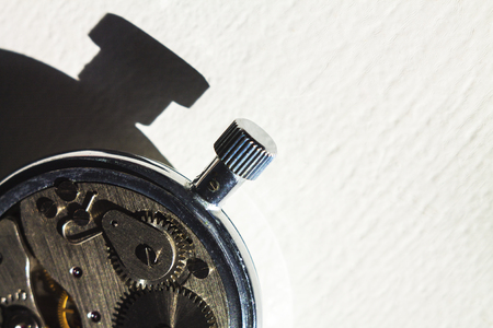 Open back of old pocket watch with sidelight and contrasting shadow.