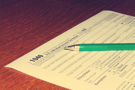 Tax day. The tax form 1040 and green pen is on a wooden table. Stock Photo