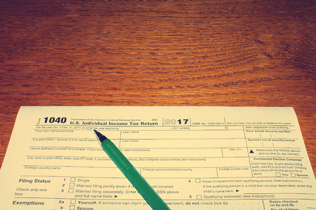 Tax day. The tax form 1040 and green pen is on a wooden table. Banco de Imagens