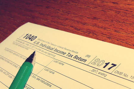 Tax day. The tax form 1040 and green pen is on a wooden table. Imagens